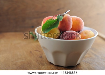 Peaches with leaves in bowl on wooden background