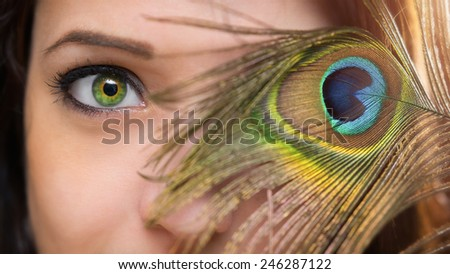 Peacock eye / Close-up photo from a young woman with peacock feather - stock photo