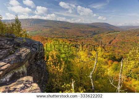 Peak Autumn Colors on Belleayre Mountain and valleys below seen from a ledge on Monka Hill in the Catskills Mountain of upstate New York. - stock photo