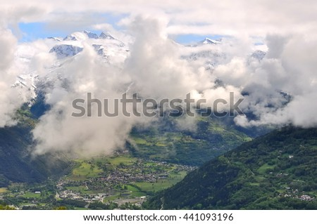 peak of mountain in the clouds in alpine  valley  - stock photo