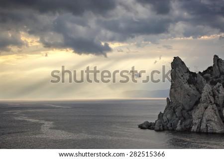 Peaked rock in sea with dramatic sky. Crimea, Novy Svet, Karaul-Oba. - stock photo