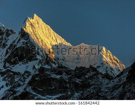 Peaks Kantega (6783 m) and Thamserku (6608 m) in the last light of the Sun (view from Tengboche monastery) - Everest region, Nepal, Himalayas - stock photo