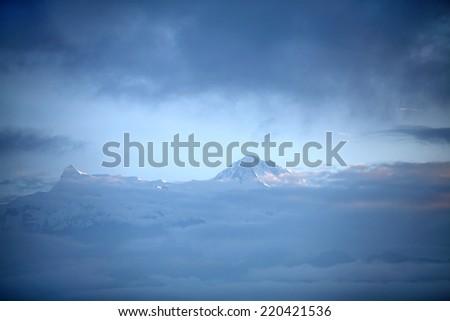 Peaks of machhapuchhre and Annapurna range seen through the clouds - stock photo
