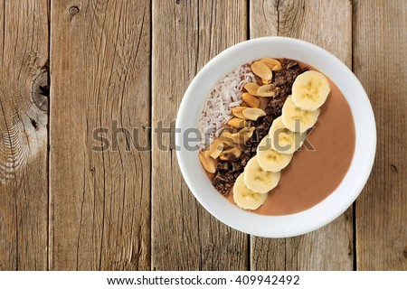 Peanut-butter banana, chocolate smoothie bowl on a rustic wooden background - stock photo