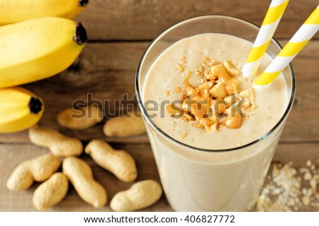 Peanut butter banana oat smoothie with paper straws on rustic table with scattered ingredients - stock photo