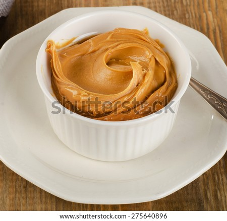 Peanut butter in a white bowl .  Shallow dof. - stock photo