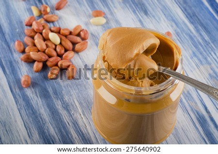 Peanut butter in  jar on a blue background.  Shallow dof. - stock photo