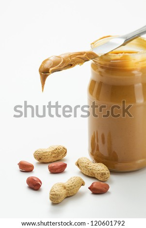 Peanut butter in jar with knife - stock photo