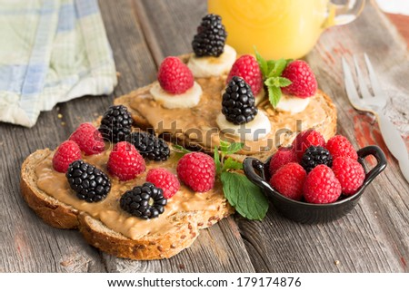 Peanut butter sandwiches on healthy wholewheat bread topped with fresh raspberries, blackberries and leafy green herbs served with a bowl of mixed berries on a picnic table - stock photo