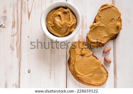 Peanut butter sandwiches or toasts  on light wooden background - stock photo