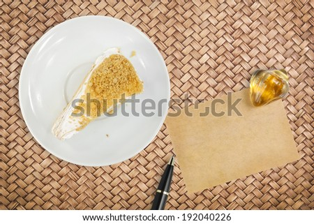 peanut meal cake with paper for note and pen on rattan table background - stock photo