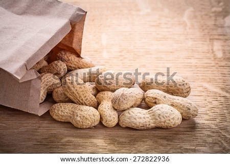 peanuts and paper bag on wooden board food and drink concept  - stock photo
