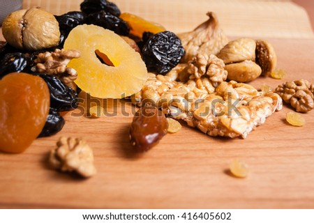peanuts honey, Grilyazh, candied roasted nuts and dried fruits, dried pineapple, dried figs, walnuts, prunes, figs, dried apricots on wooden table - stock photo