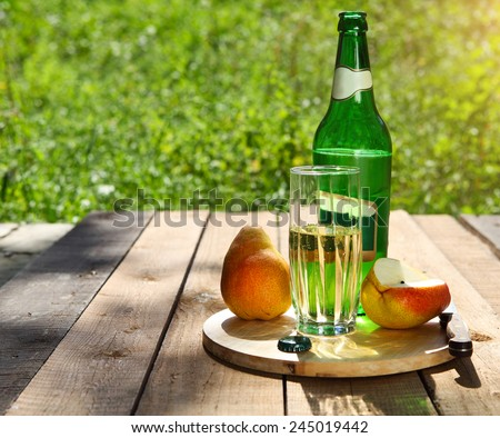 Pear cider and pears on the summer picnic in the garden - stock photo