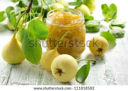 Pear jam in a glass jar and fresh fruits with leaves - stock photo