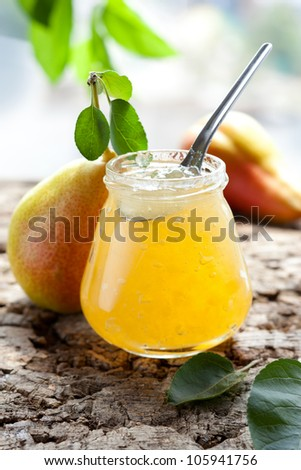Pear jam in jar with spoon - stock photo