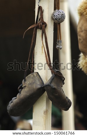 Pear of old-fashioned leather shoes hanging on a wooden post