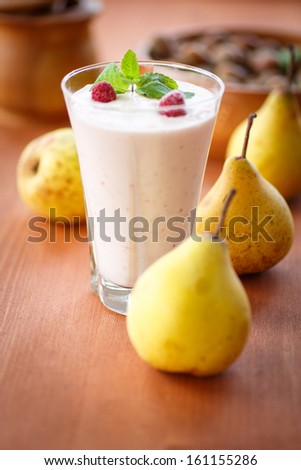 pear smoothie with berries and mint in a glass