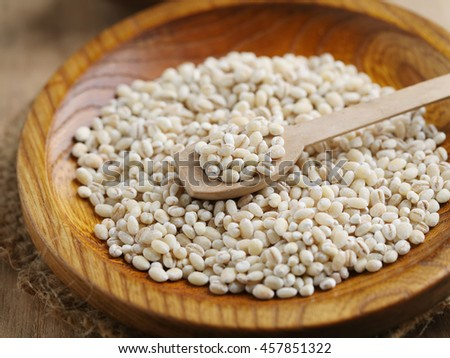Pearl barley grain seeds on wooden plate.