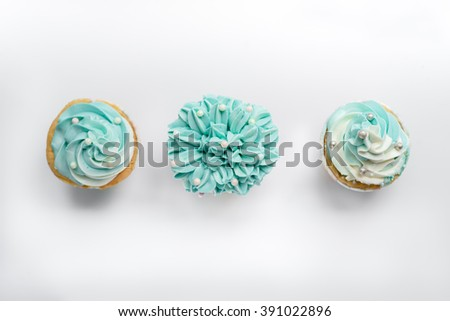 Pearl birthday cupcake with butter cream icing on gray background, top view. - stock photo