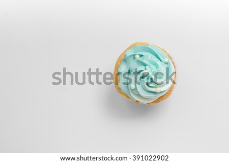 Pearl birthday cupcake with butter cream icing on gray background, top view.