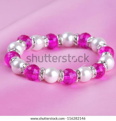 pearl bracelet on pink silk background - stock photo