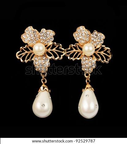 pearl earrings flower shape over black background - stock photo