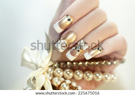 Pearl French manicure with rhinestones and embellishments. - stock photo