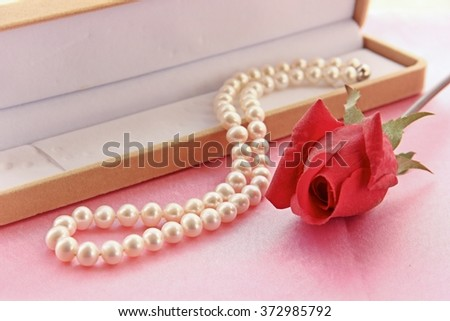 Pearl necklace and artificial red rose with jewel box on pink background.