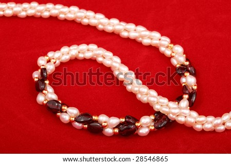 Pearl necklace on red background