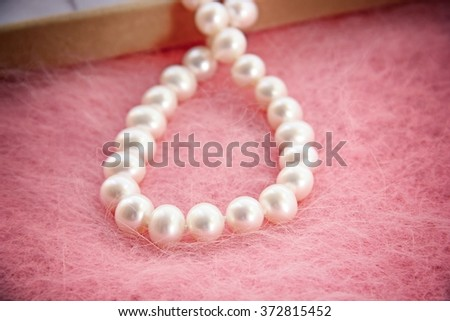 Pearl necklace with jewel box on pink background. - stock photo