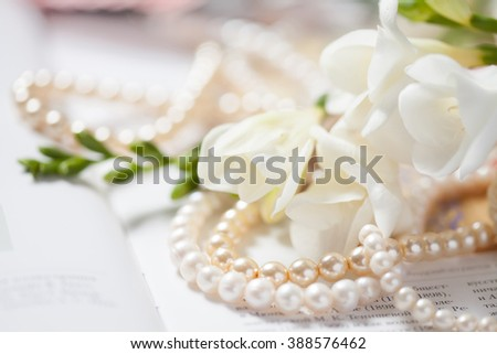 pearl necklace with white flowers on book, macro - stock photo