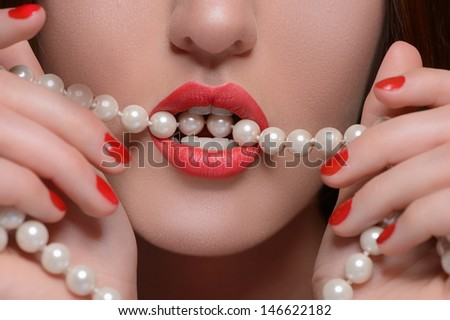 Pearl white teeth. Close-up of beautiful women holding pearl necklace in her mouth - stock photo