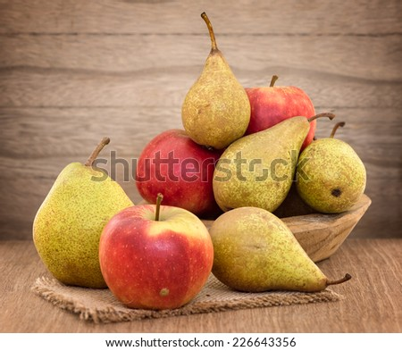 Pears and apples in a basket on wood table - stock photo