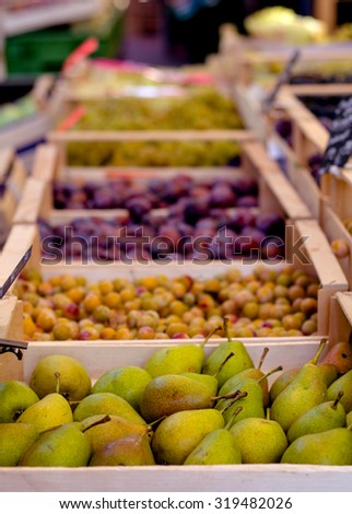 Pears and other fruits and vegetables in wooden cartons in a farmer's market.
