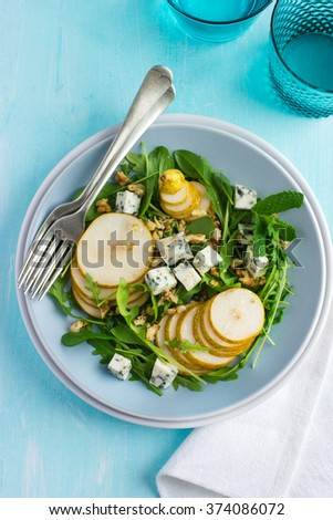 pears, arugula and  blue cheese salad on blue background, top view - stock photo