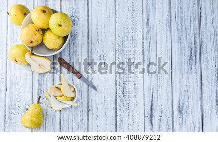 Pears (selective focus) on an old wooden table (close-up shot) - stock photo