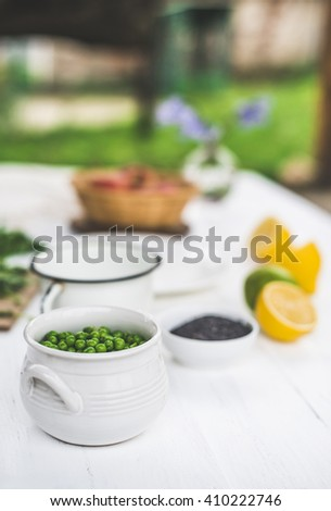 Peas in a bowl on white wooden table. Dressing of lime and sesame oil.