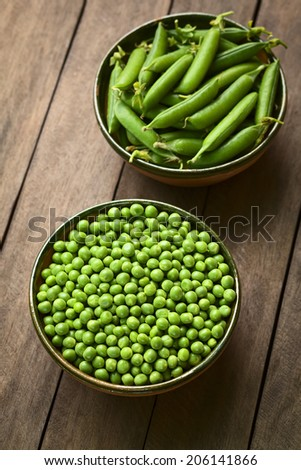 Peas (lat. Pisum sativum) and closed peapods in bowls (Selective Focus, Focus on the lower half of the peas in the bowl) - stock photo