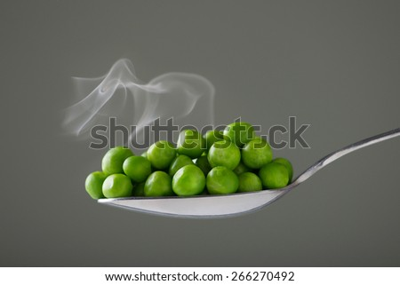Peas on a spoon with steam on a grey background - stock photo
