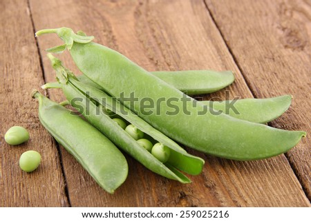 Peas on rustic wooden table - stock photo