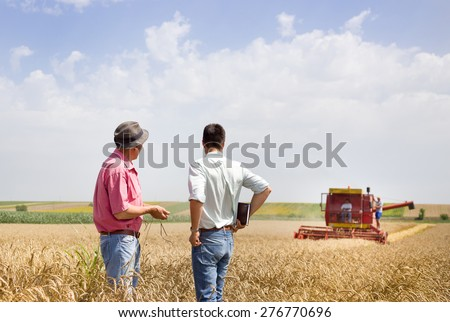 Peasant and business man talking on wheat field during wheat harvest - stock photo