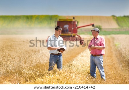 Peasant and businessman making deal on wheat field - stock photo
