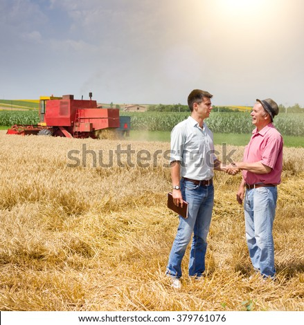 Peasant and businessman shaking hands on wheat field - stock photo