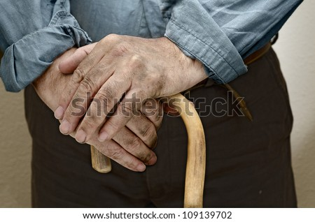 Peasant hands, leaning on a cane placed in front of him