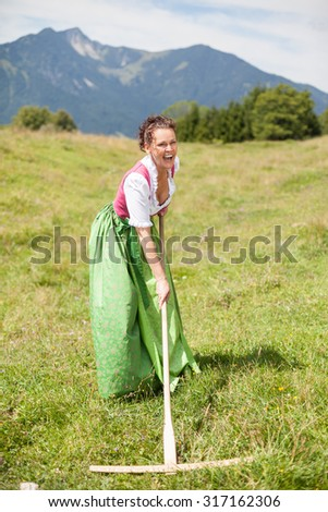 Peasant woman in middle age in dirndl having fun while working on a mountain meadow with a rake - stock photo