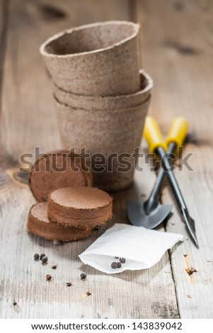 Peat bricks and pots, seeds and garden tools - stock photo