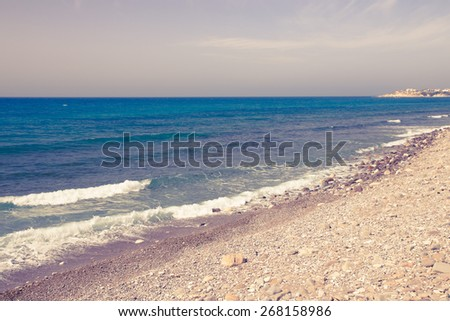 Pebble beach and blue water of the Mediterranean Sea. Toned.