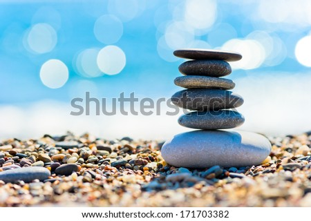 pebble beach and gray spa stones in the form of a tower - stock photo
