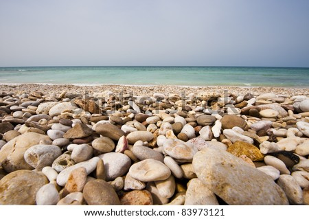Pebble beach on the coastal road between Quriat and Sur in Oman. - stock photo